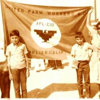 Jesus & Sara with sons display handcrafted flag at Forty Acres in Delano / 1970
