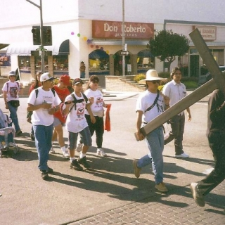 Father Victor Salandini carries his cross. / Delano / 1994